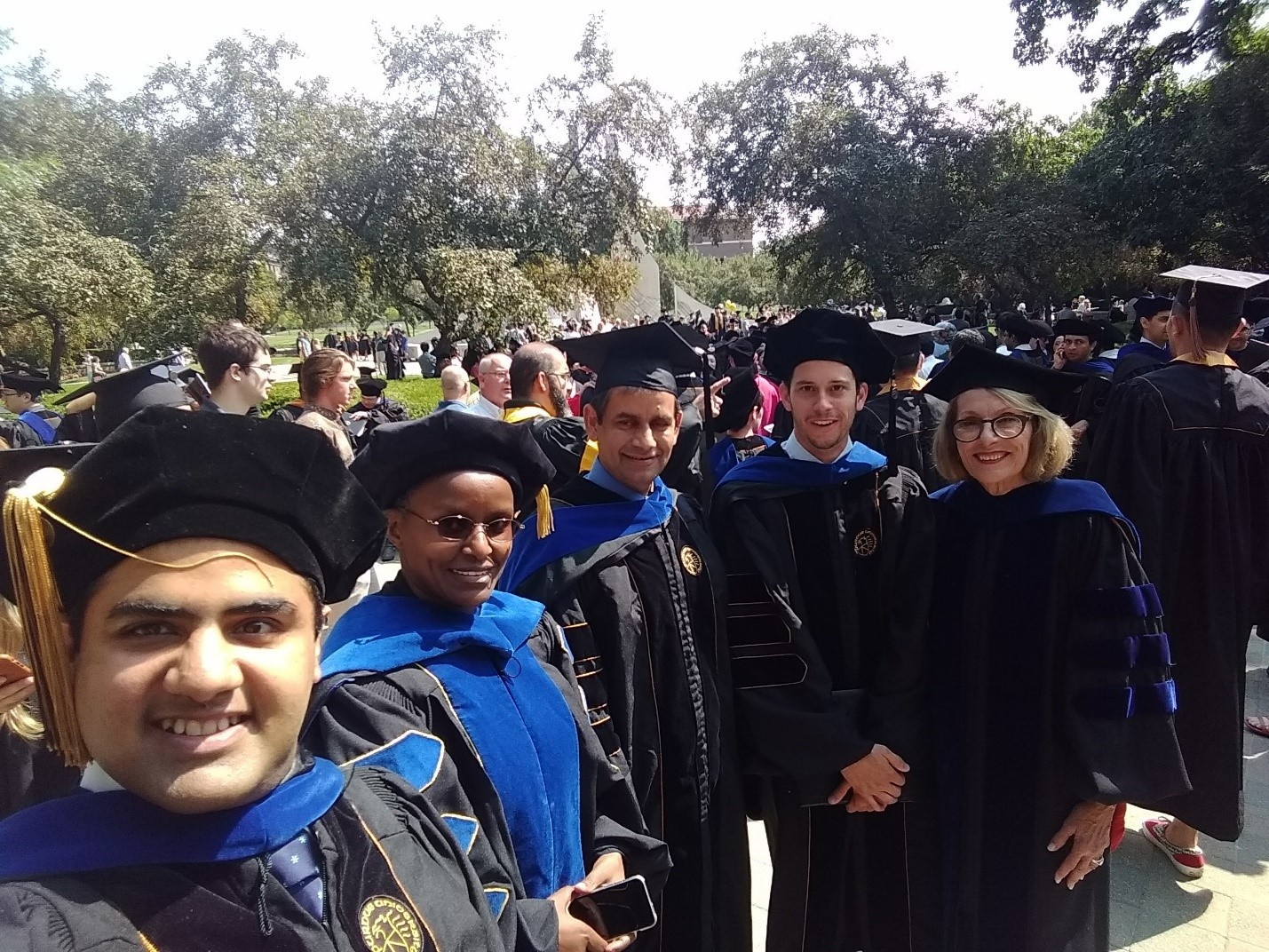 Student and faculty taking a selfie in a graduate procession