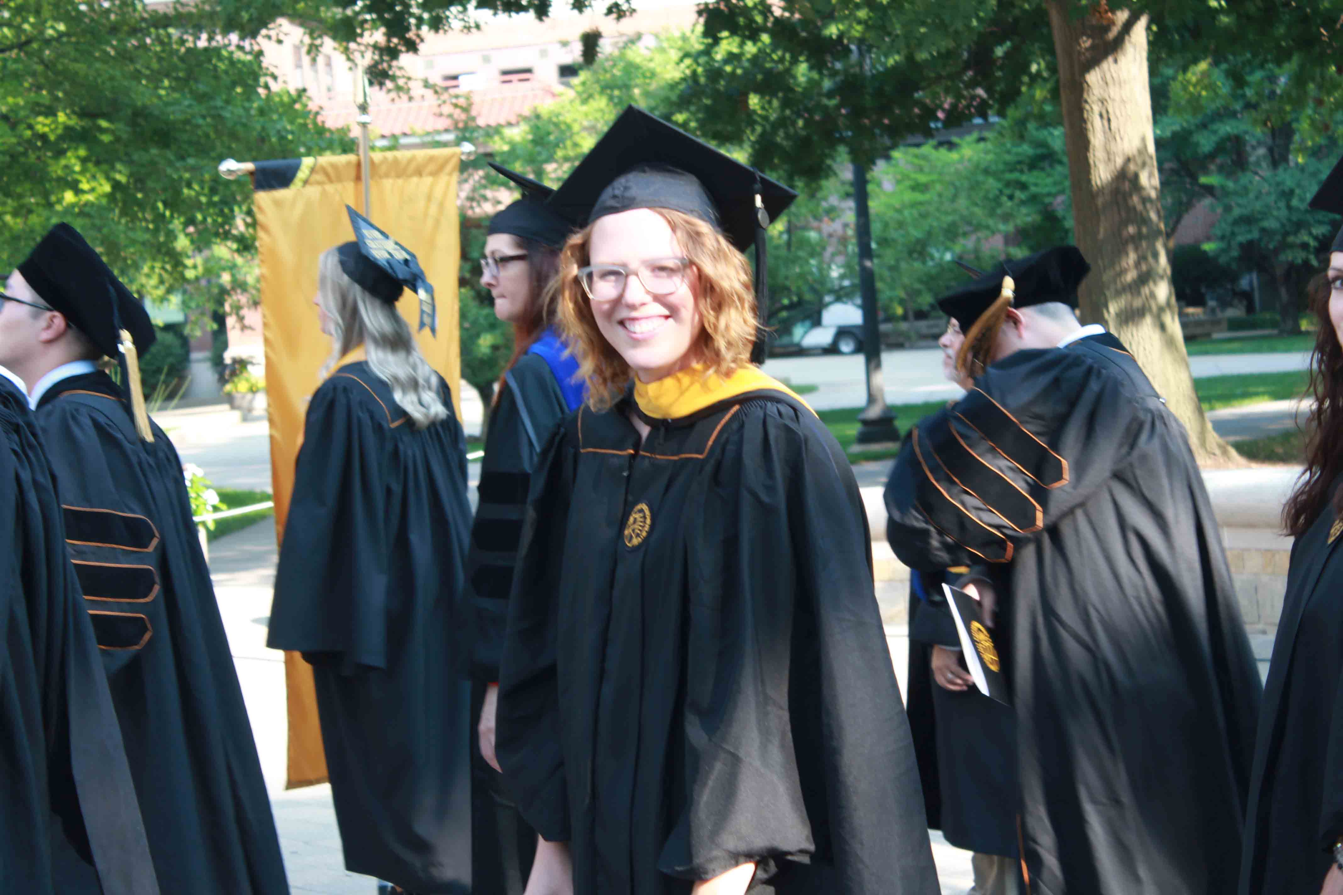 Woman smiling in line for graduate procession