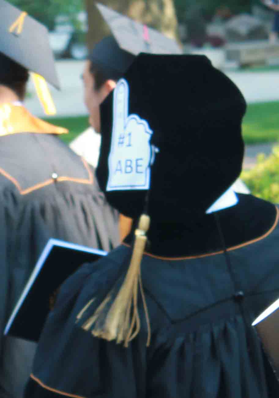 Graduating student with a #1 ABE sign on her back