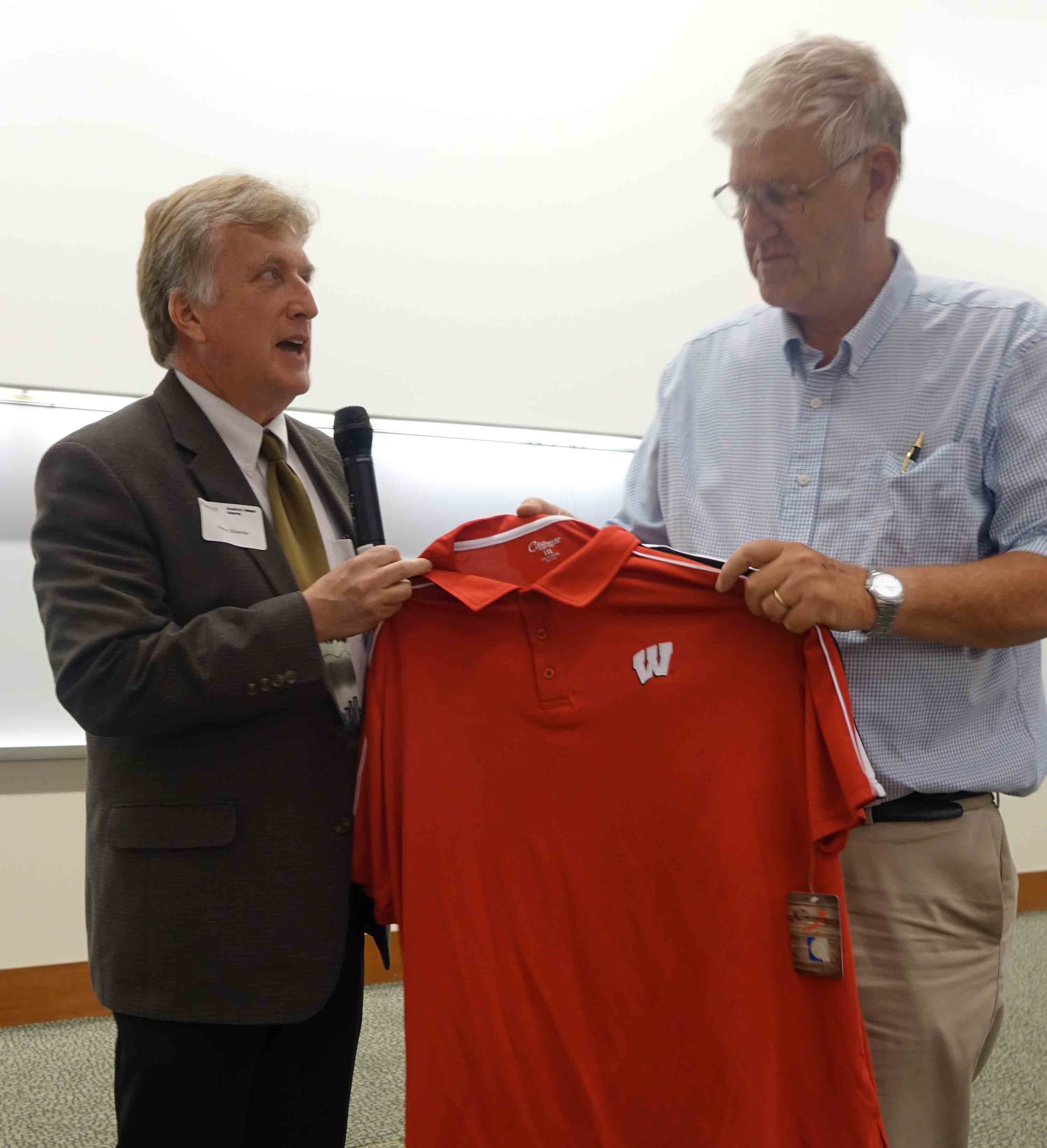Dr. Shutske presents Professor Gary Krutz with a Wisconsin polo shirt