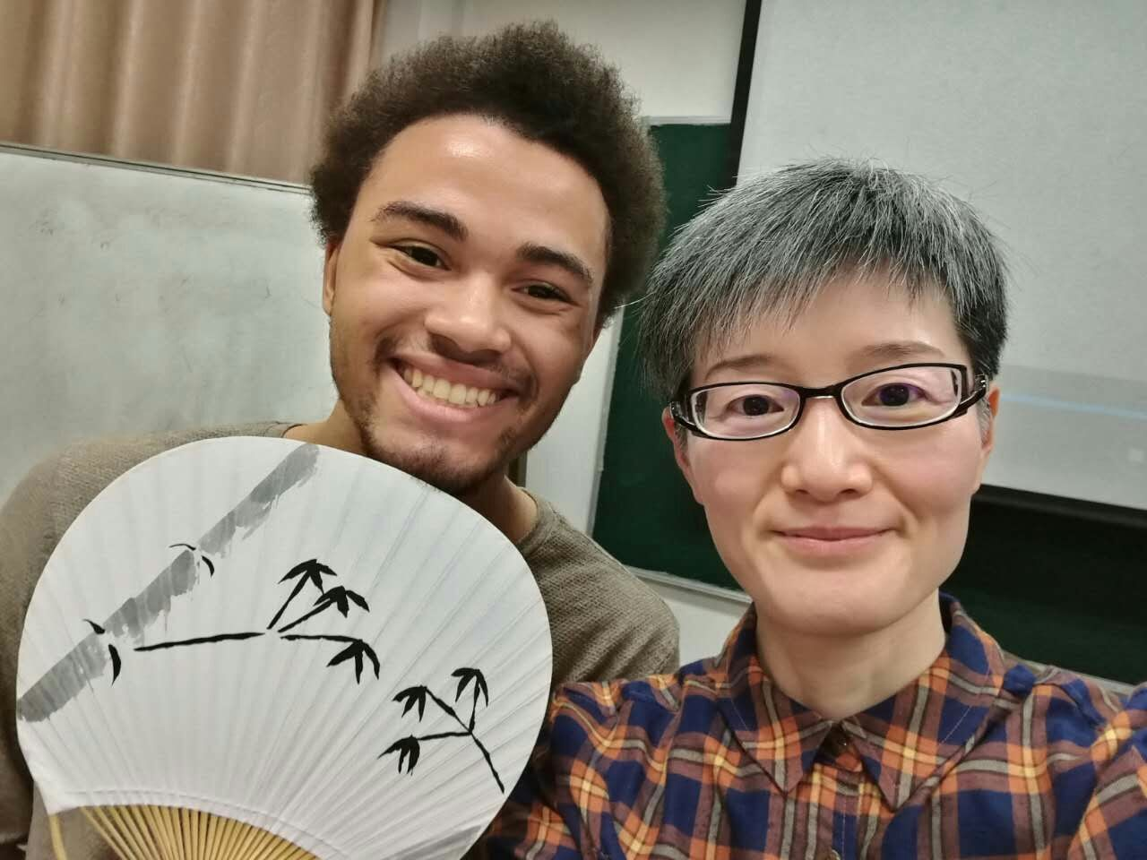 During a culture class field trip, SJTU program participant Jerome Alexander Marshall (left) learned how to paint traditional bamboo trees on fans.