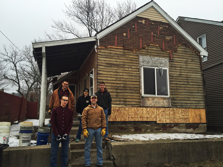 Members of Beta Tau stand in front of an abandoned house they worked on with Habitat for Humanity
