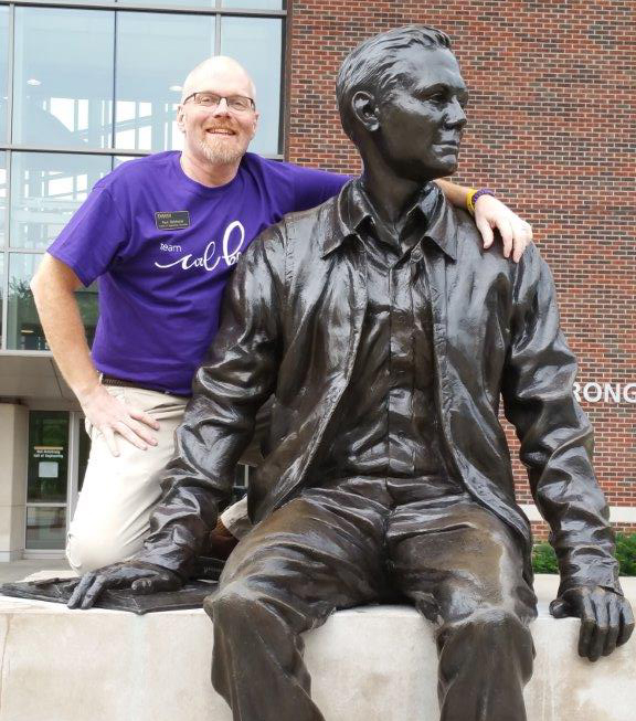 Paul Birkhimer posing at Neil Armstrong Statute outside of Armstrong Hall