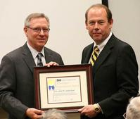 John Sutherland (right) receiving the award from 2011 SAE International President Richard E. Kleine