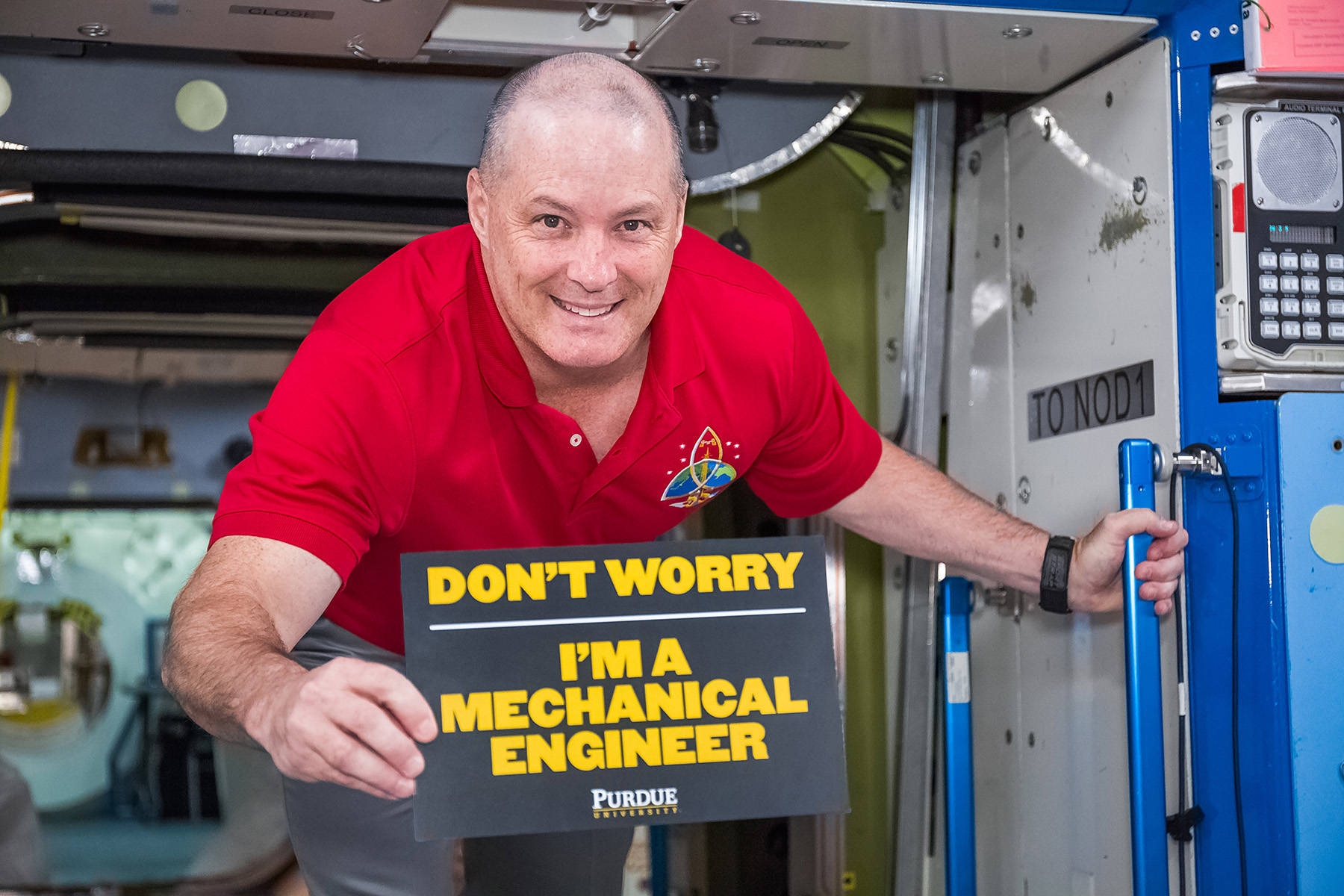 Scott Tingle holding up a sign that says - Don't worry, I'm a Mechanical Engineer - Purdue University