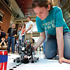 Young woman setting up her robot for competition