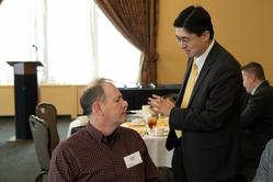 Robert Frosch (L) speaks with Dean Mung Chiang (standing)