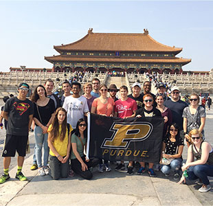 Purdue Students holding a flag with Great Wall of China behind them