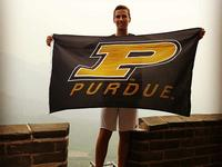 Student standing on the Great Wall holding a Purdue Flag