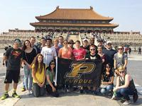 Students in from of a temple in China holding a Purdue Flag
