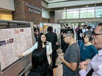 Photo of Xiang Feng presenting poster