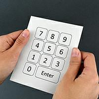 Hands holding a number keypad printed on paper