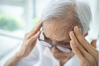 elder person holding their forehead in both hands