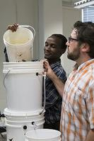 John Maiyo and John Howarter pour water into a slow sand filter