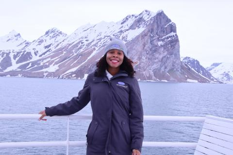 Jessica Fleming on the National Geographic Lindblad Explorer Ship standing in front of iceburgs.