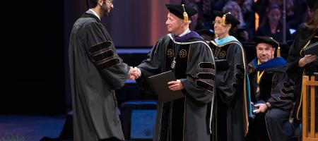Purdue University Mitchel Daniel shaking student hand at commencement